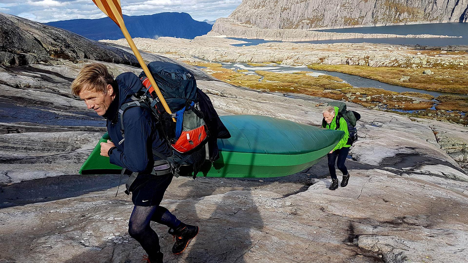Menn som bærer kano i fjellet